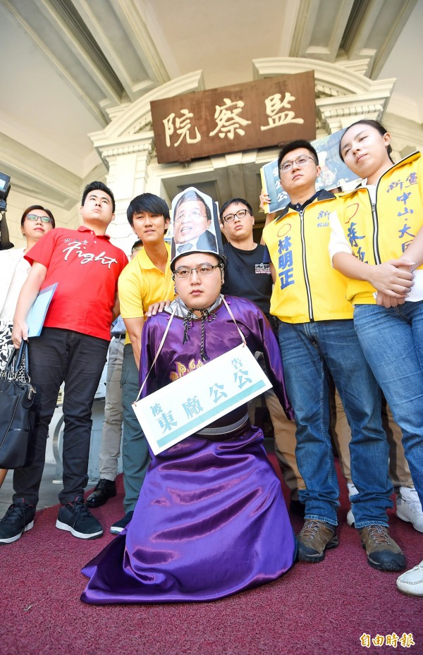 New Party members perform a skit in front of the Control Yuan in Taipei yesterday as they a file a request for an investigation into what they called administrative bias at the Transitional Justice Commission. Photo: Fang Pin-chao, Taipei Times