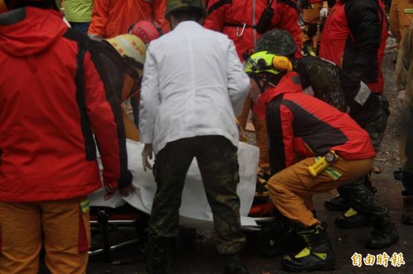 周志軒被搜救人員救出時已無生命跡象,被蓋上白布。(記者林欣漢攝)