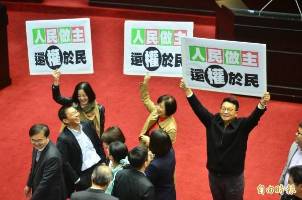 立法院公投法修正案三讀通過,民進黨立委們拿著看板海報歡呼。(記者王藝菘攝)