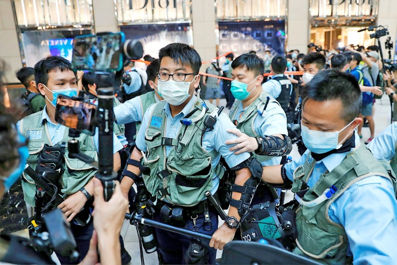 Police officers yesterday ask people in Hong Kong to leave a protest, after China passed a national security law for the territory. Photo: Reuters