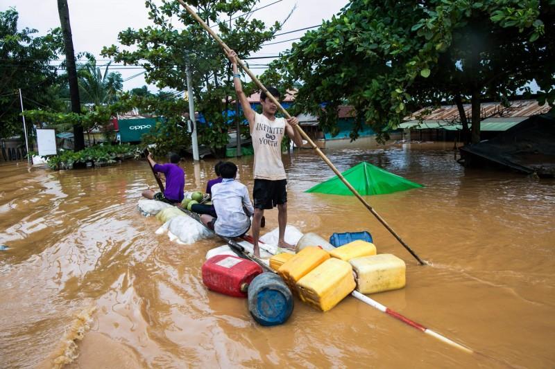 緬甸近日因暴雨發生多起土石流,其中東南部城市孟邦至少有52人因水患罹難。圖為孟邦的居民乘船避難。(法新社)