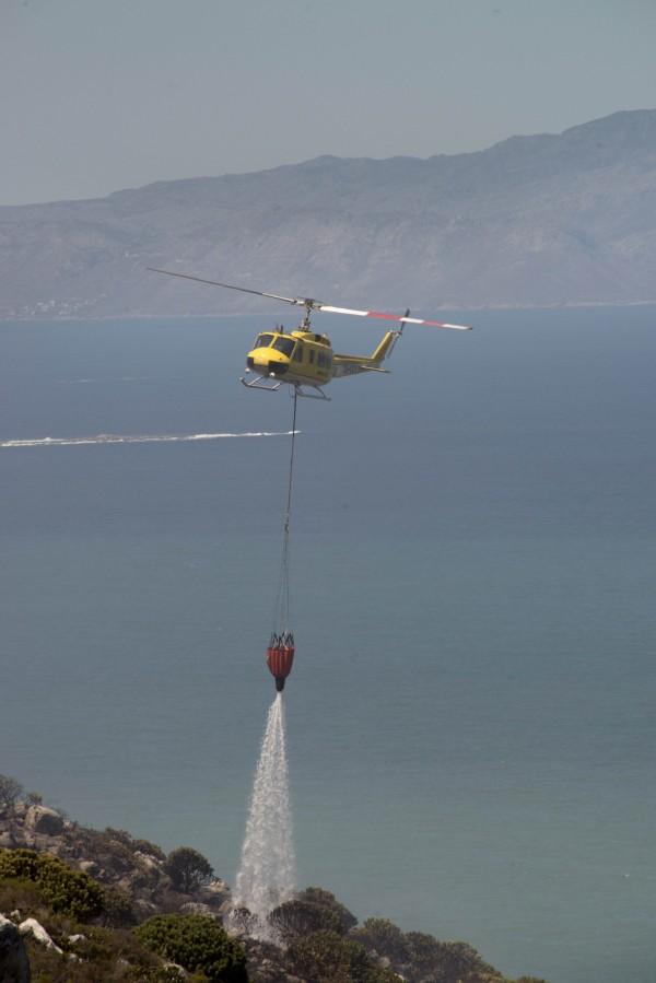 由於消防車遲遲無法進入災區,有關單位出動直升機自大西洋撈取海水,傾倒在桌山國家公園內。(法新社)