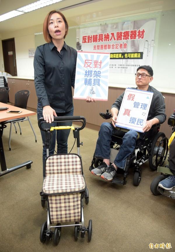 中華民國身心障礙聯盟等多個團體31日下午舉行「反對輔具納入醫療器材」聯合記者會,秘書長滕西華(左)現場說明行動輔具將受到的相關影響。(記者黃耀徵攝)