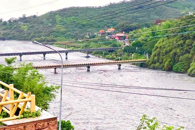 A rain-swollen river sweeps beneath bridges in Pingtung County's Majia Township yesterday. Photo courtesy of Majia Mayor Liang Ming-hui