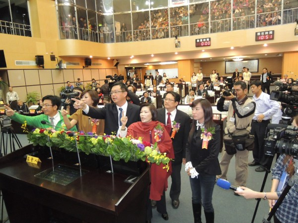 民進黨多位議員為大會主持人推選方式跑到發言台前與主席洪玉鳳爭論。(記者王俊忠、洪瑞琴攝)