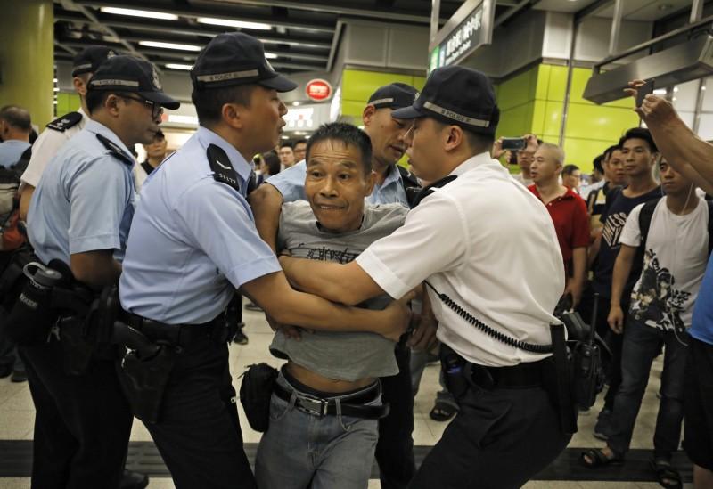 圖為香港「反送中」群眾30日發起「全港大塞車」的不合作運動,警察阻擋想和反送中示威者理論的民眾。(美聯社)