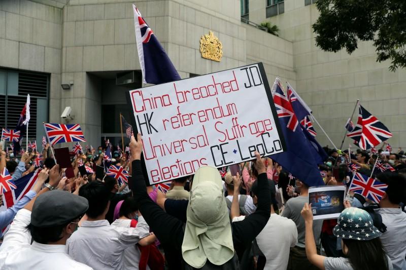 有些人高舉標語,指責中國違反「中英聯合聲明」,並要求香港落實「真普選」。(路透社)