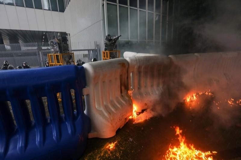 金鐘政總的充水式護欄後方出現火光。(美聯社)