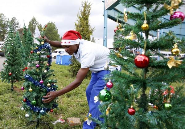 炎熱的非洲國家辛巴威,1名男子穿著短袖,在艷陽下裝飾他的耶誕樹。(歐新社)