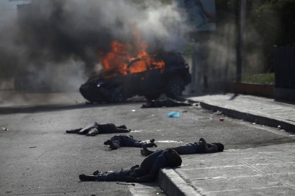 海地示威抗議現場發生政府車衝撞人群事件,造成至少6人死亡,涉事車輛隨即遭民眾焚毀。(美聯社)