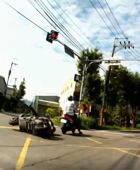 兩車撞擊後,黑衣騎士馬上連人帶車倒地,被撞駕駛則往前滑行到路邊。(圖擷自爆料公社)