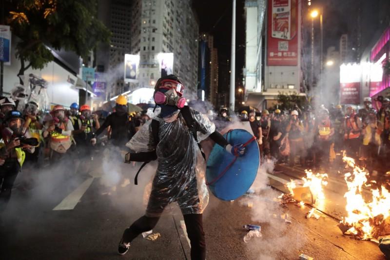 示威者手持圓盾防衛,回擲催淚彈至警方防線。(美聯社)