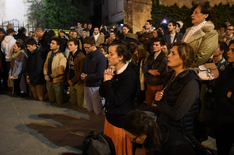 法國巴黎聖母院燃起熊熊大火,現場民眾徹夜未眠緊盯救火進度,有人不斷流淚不能自己,更有民眾說「巴黎再也回不去原來的樣子」、「我們的歷史正消逝在煙塵中」。(法新社)