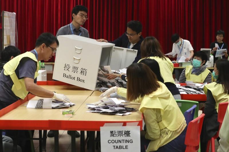週日,香港大批選民參加了區議會選舉。此次選舉被視為公眾對民主抗議活動支持程度的民意公投。圖為香港一個投票站的工作人員正在倒空投票箱清點選票。(美聯社)