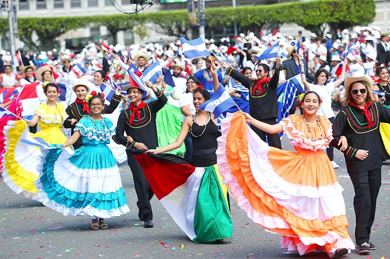 Hondurans wearing traditional costumes wave flags as they parade past the Presidential Office Building in Taipei yesterday. Photo: CNA