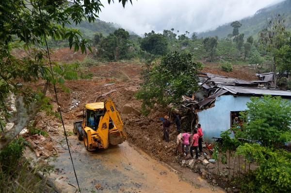 土石流造成道路嚴重毀損,導致挖土機等救難裝置難以運抵該區,使得救援工作嚴重受阻。(法新社)
