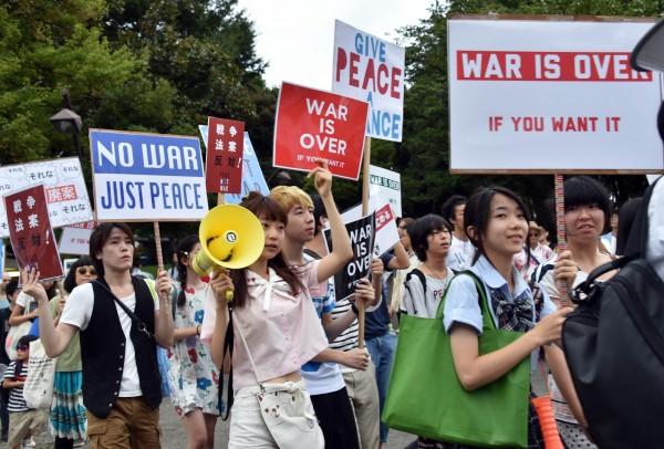 配合選舉年齡下修到18歲,日本文部科學省5日宣布「開放學生在課後參與政治活動」。圖為高中學生參與9月反安保法運動。(法新社)
