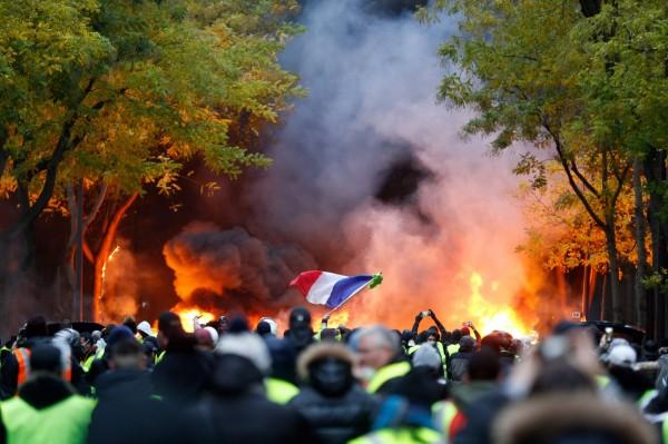 法國「黃背心」運動越演越烈,民眾上巴黎街頭焚燒車輛抗議。(法新社)