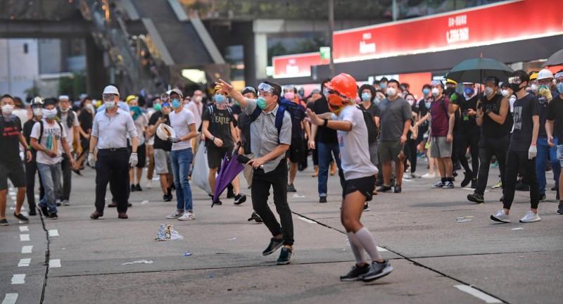 香港群眾12日上午起占據立法會周邊區域道路,堅定表達「反送中」立場,警方下午陸續投射催淚彈欲驅離人潮,有抗議人士撿起催淚彈反擊,丟向警方所在處。(中央社)