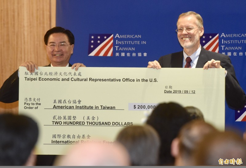 「美台印太區域民主治理諮商」會議12日在美國在台協會舉行,外交部長吳釗燮(左)代表捐款,由美國在台協會處長酈英傑(右)代表接受。(記者簡榮豐攝)
