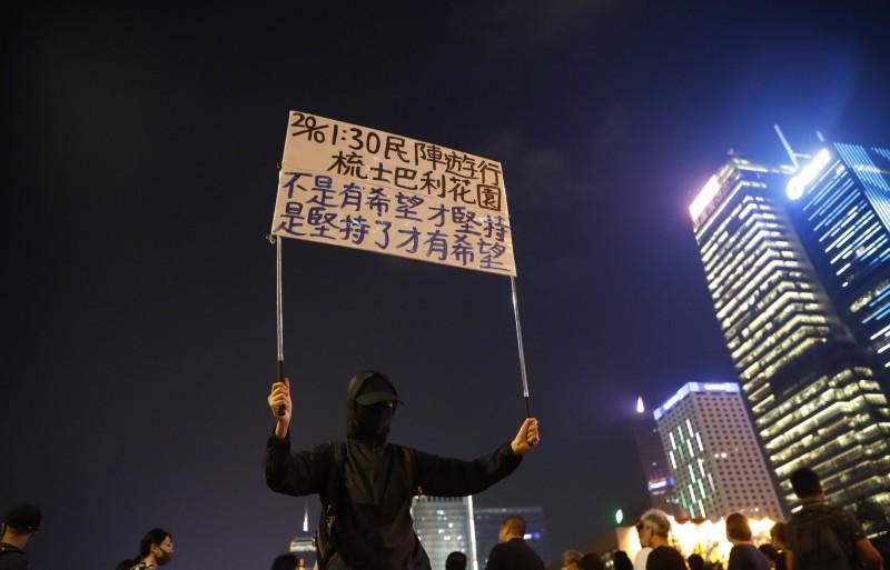 原由香港民陣主辦的九龍遊行,遭警方發出反對通知書,上訴後又被駁回,但今日4人宣布將以個人名義承辦,照常舉行。圖為香港示威者舉牌宣傳。(歐新社)