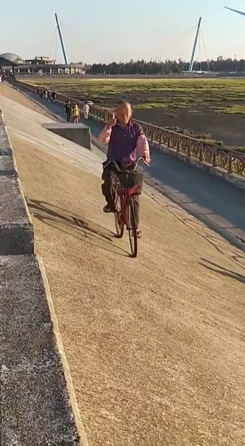 1名阿伯被遊客發現穩穩地將腳踏車騎在與地面呈45度的坡地上,詢問他訣竅,阿伯稱「心無罣礙」,令民眾與網友直呼厲害。(圖擷取自爆廢公社)