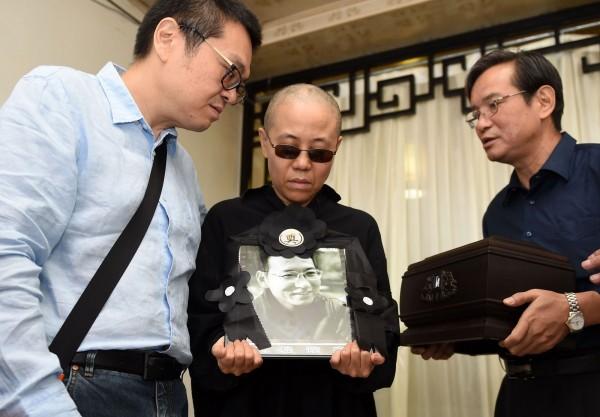 中國民主鬥士劉曉波病逝,中國當局趕在今日將他遺體火化,並在隨後舉辦簡易告別式。圖為劉曉波的妻子劉霞捧著劉曉波的遺照。(法新社)