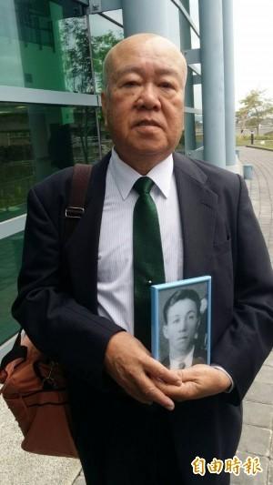 日人青山惠昭今上午帶著其父遺照出庭聆判。(記者楊國文攝)