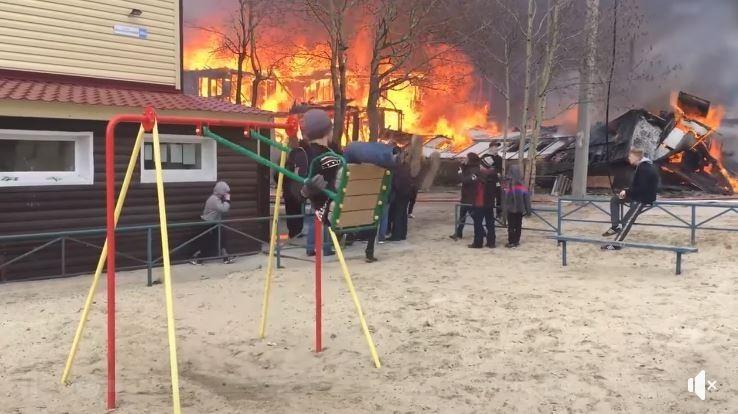 俄國9歲男童在火警現場旁邊,若無其事地盪鞦韆,影片曝光被網友推爆。(圖擷取自影片)