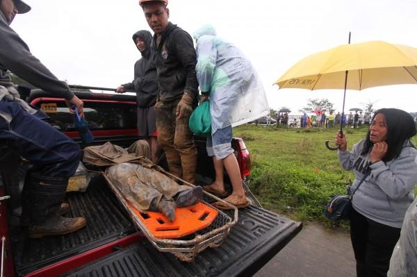 越來越多死者被從土石堆中挖出。圖為搜救隊從山崩後的土石堆中,搬出1具罹難者遺體。(法新社)