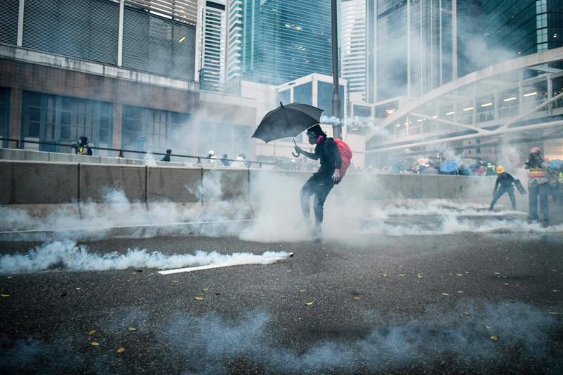 根據港警提供數據,截至目前為止,港警已向示威者發射1800多枚催淚彈。圖為一名示威者在警方丟出催淚彈後做出反應。(法新社)