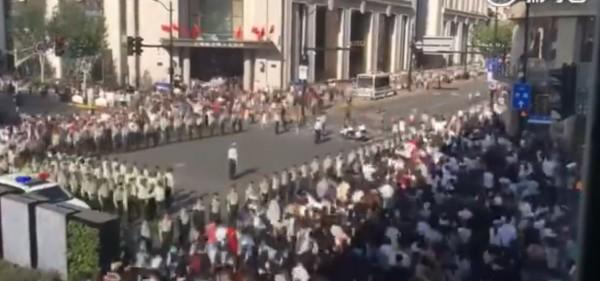 上海市為免十一長假出交通亂象,出動大批武警在路上形成人肉柵欄維護秩序。(圖擷取自微博)