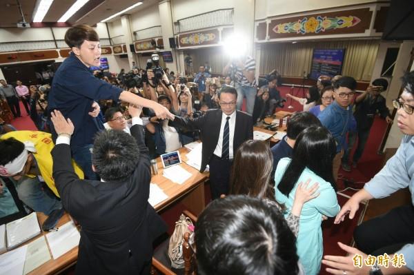 陳瑩突宣布休息並試圖離席,勞工代表們見狀湧上並翻越主席台。(記者方賓照攝)