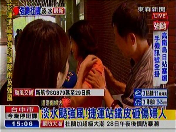 一名婦人今在淡水捷運站竟遭強風吹落的鐵皮砸傷肩膀及背部。(圖擷自東森新聞)