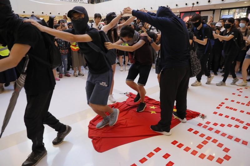 群眾以「火車過山洞」的方式輪流踐踏中國五星旗。(美聯社)
