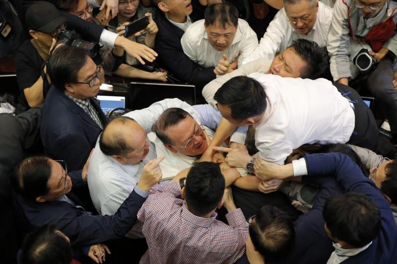 香港立法會今(11日)修訂「逃犯條例」,民主派和親北京的建制派陷入混戰,泛民主派的議員范國威跌倒送醫。圖為雙方人馬拉扯。(美聯社)