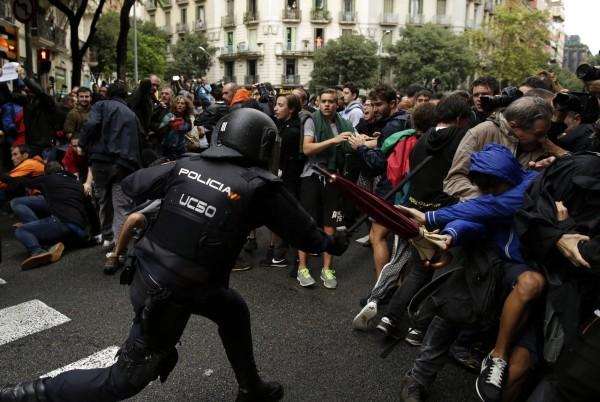 鎮暴警察揮舞警棍驅離阻礙民眾。(美聯社)