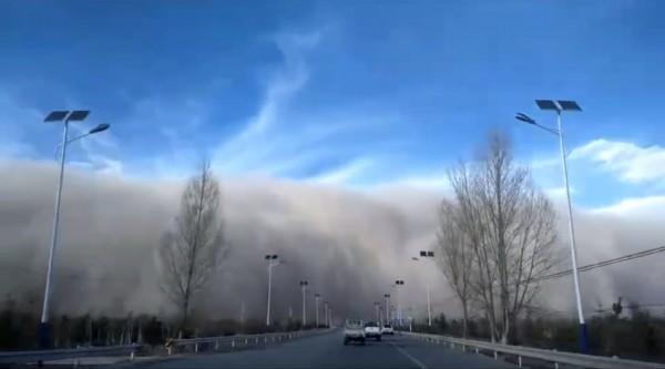 昨日中國甘肅的沙塵高度竟然高得像座牆,畫面就像是災難片場景一般。(圖擷取自環球網)