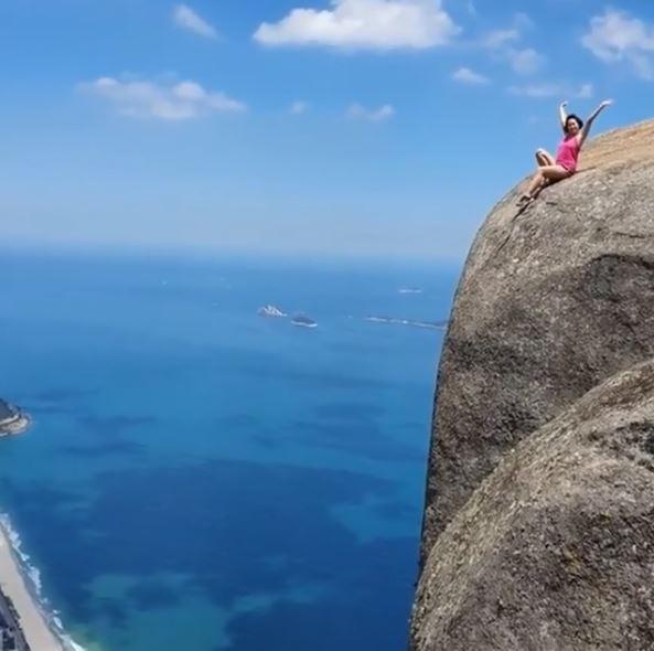 巴西里約熱內盧(Rio de Janeiro,簡稱里約)自然景點「桅帆岩」(Gávea Rock),因岩頂能俯瞰整座城市,不但深受旅客歡迎,也成為「打卡勝地」,卻出現許多旅客為了「照片效果」罔顧安全,直接坐在懸崖邊拍照、錄影,畫面驚險。(圖擷取自IG @gres_big_family)