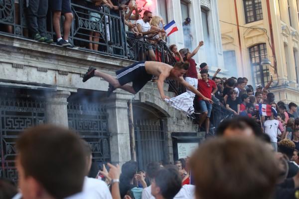 有球迷乾脆直接攀上路燈與民宅屋頂上慶祝國家隊的奪冠。(歐新社)