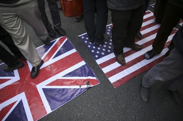 群眾踩踏美國國旗洩憤。(美聯社)