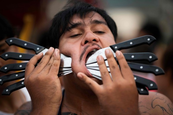 許多信眾會用各式各樣的刀片、釘子或任何金屬物品次穿臉頰和舌頭。(法新社)