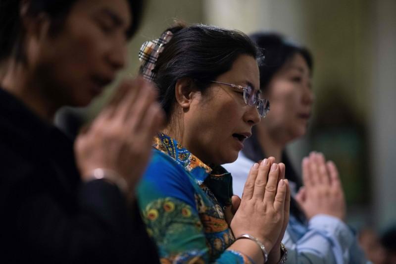 中國嚴格控制宗教活動,基督教徒就算是救援災區、義診或發名片,全都被逮捕。圖為中國基督徒祈禱的場景。(法新社)