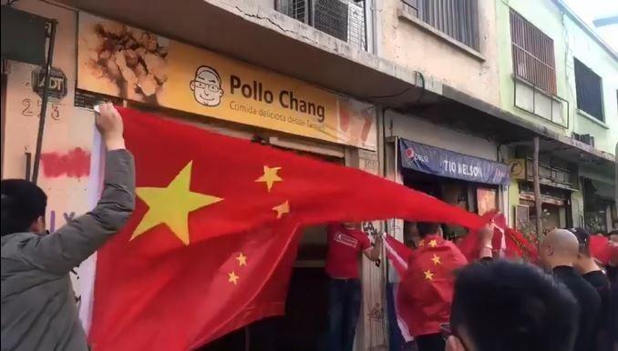 中國人在「Pollo Chang」店面前高唱中國國歌。(擷取自微博)