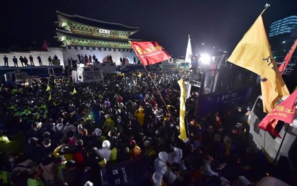 南韓民眾在光化門廣場前抗議世越號事件,可見警員使用車輛將廣場入口擋住。(法新社)