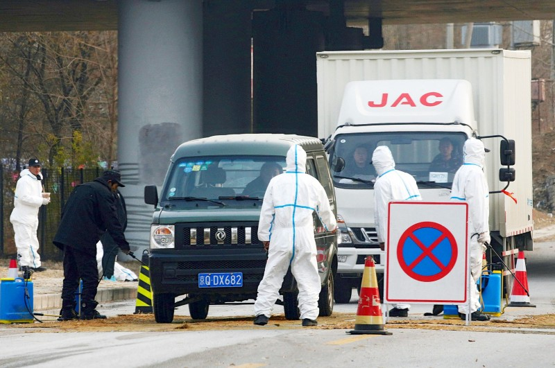 Workers in protective suits check vehicles on a road leading to a village near a farm where African swine fever was detected in Fangshan district of Beijing on Nov. 23 last year.   Photo: Reuters