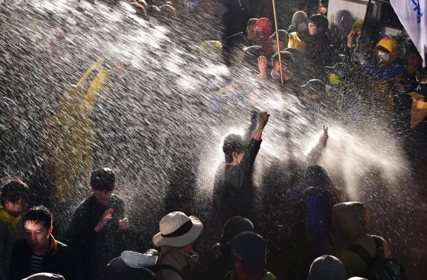 面對鎮暴水車的攻擊,民眾紛紛轉身以背部迎向水柱,以免受傷。(法新社)