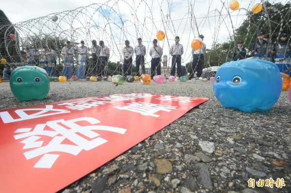 「2017秋鬥」隊伍行進到總統府前方後停下,掙脫鐵鍊表達人民的覺醒,最後將400多隻小豬鋪滿丟向總統府。(記者廖振輝攝)