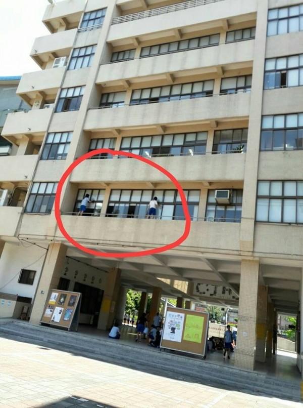 有網友PO出高中生擦玻璃的照片,認為看起來有點太危險。(圖擷自爆料公社)