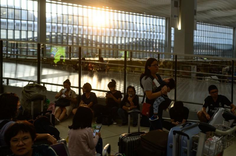 香港機場導致航班大亂,但有受困旅客聲援反送中抗議群眾。圖為旅客在機場休息。(法新社)